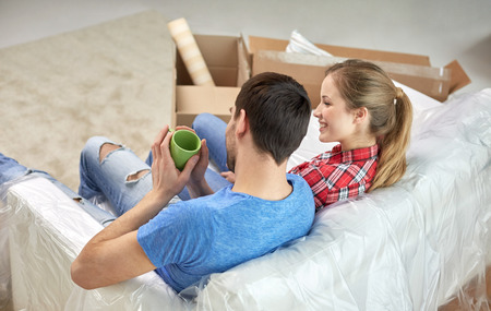 first move: moving, home, repair and people concept - happy couple relaxing and sitting on sofa with cups in new apartment