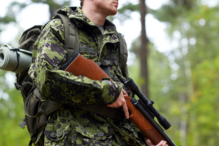 狩猟、戦争、軍隊と人民のコンセプト - 銃を保持し、森を歩く若いハンターやレンジャーの兵士の手のクローズ アップ