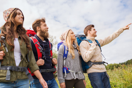adventure travel: adventure, travel, tourism, hike and people concept - group of smiling friends walking with backpacks Stock Photo