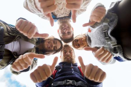 여행, 관광, 하이킹, 제스처 및 사람들이 개념 - 원 안에 서 서 야외에서 엄지 손가락을 보여주는 배낭을 가진 웃는 친구의 그룹 스톡 콘텐츠