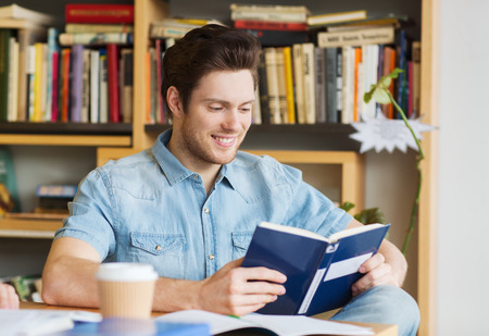 reading book: people, knowledge, education and school concept - happy student reading book and drinking coffee in library Stock Photo