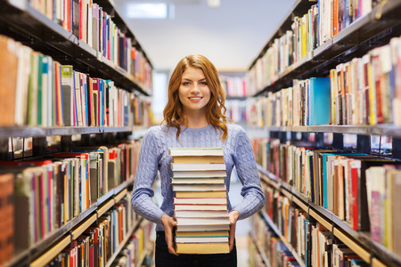 library book: people, knowledge, education and school concept - happy student girl or young woman with stack of books in library