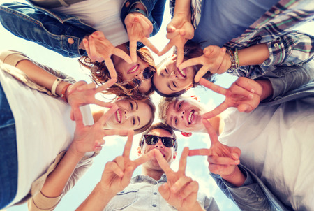 girls friends: summer holidays and teenage concept - group of teenagers showing peace or victory gesture