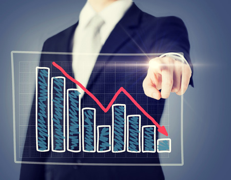 going down: business and technology concept - businessman hand with chart on virtual screen