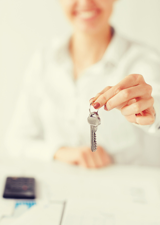 bisiness: business, banking, real estate concept - woman hand holding house keys