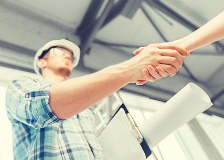 arquitectura y reformas del hogar concepto - constructor con el modelo socio agitando la mano