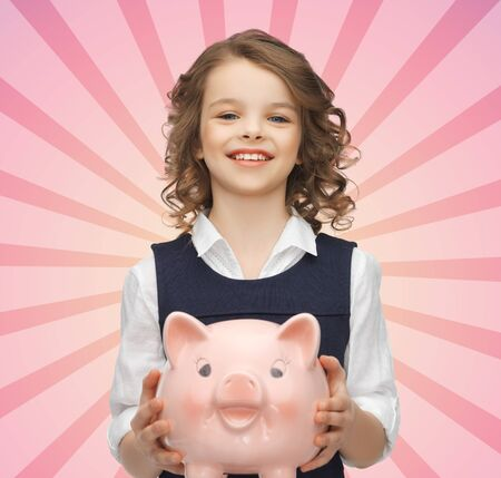thrifty: people, money, finances and savings concept - happy girl holding piggy bank over pink burst rays background