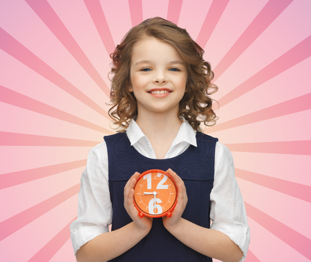 puntualidad: la gente, la infancia, el tiempo y el concepto de puntualidad - ni�a feliz con reloj de alarma sobre fondo rosa rayos r�faga Foto de archivo