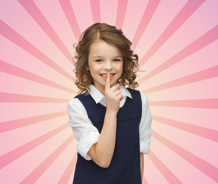 people, children, secrecy and mystery concept - happy girl showing hush gesture over pink burst rays background photo