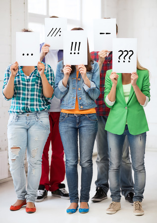 pretense: people, emotions and communication concept - group of friends or students covering faces with paper sheets Stock Photo