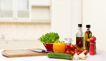 調理、静物、食品、健康的な食べるコンセプト - 新鮮な熟した野菜、スパイス、台所用品キッチンの背景の上のテーブルの上