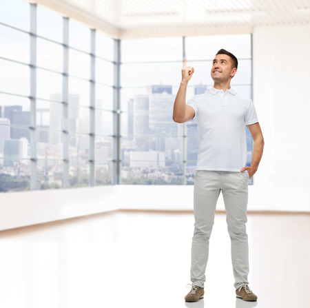 empty room background: real estate, sale, business, gesture and people concept - smiling man pointing finger up over empty apartment or office room with big window and city view background Stock Photo