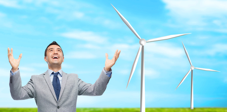 business, people, alternative energy and development concept - happy businessman in suit with raised hands laughing and looking up over blue sky and windmills background photo