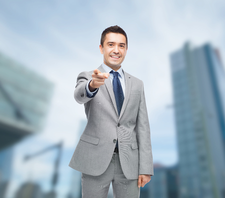 business, people and office concept - happy smiling businessman in suit pointing at you over city background