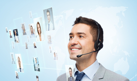 conference call: business, people, technology and customer service concept - smiling businessman in headset looking to virtual contacts icons projection over blue background