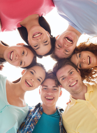 friendship, youth and people - group of smiling teenagers in circle