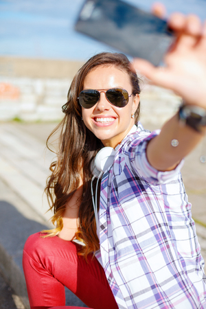 holidays and tourism concept - smiling teenage girl taking picture with smartphone camera aoutdoors photo