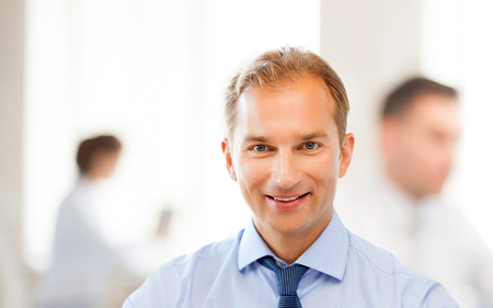middleaged: smiling middle-aged businessman in office
