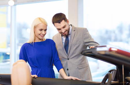 auto business, car sale, consumerism and people concept - happy couple buying car in auto show or salon photo