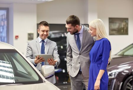 buy car: auto business, car sale, technology and people concept - happy couple with car dealer in auto show or salon