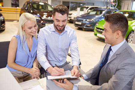 selling service smile: auto business, sale and people concept - happy couple with dealer buying car and signing documents in auto show or salon