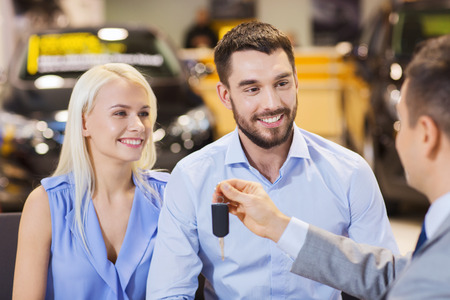 auto business, sale and people concept - happy couple with dealer giving car key in auto show or salon photo