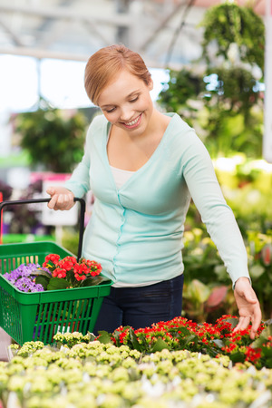 consumerism: people, gardening, shopping, sale and consumerism concept - happy woman with basket choosing and buying flowers in greenhouse