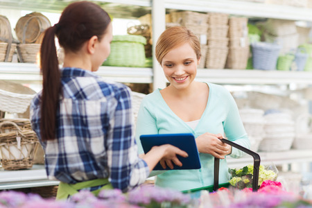 helping people: people, gardening, shopping, sale and consumerism concept - happy gardener with tablet pc helping woman with choosing flowers at flower shop