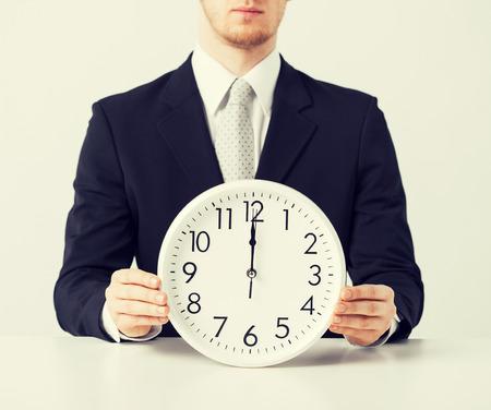 oclock: close up of man holding wall clock