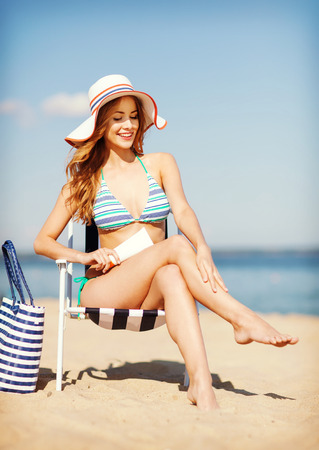 chaise longue: summer holidays and vacation - girl putting sun protection cream on the beach chair