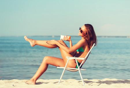 夏の休暇、祝日、人々 のコンセプト - ビーチで日光浴ラウンジで若い女性を笑顔