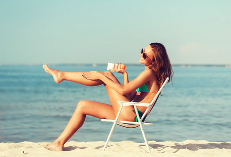 sun protection: summer vacation, holidays and people concept - smiling young woman sunbathing in lounge on beach