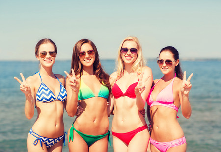 peace sign: summer vacation, holidays, gesture, travel and people concept- group of smiling young women showing peace or victory sign on beach Stock Photo