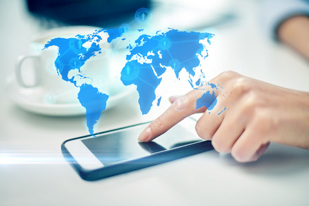 business, technology, global communication and people concept - close up of woman hand with smartphone and coffee pointing finger to screen over world map projection