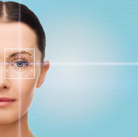 laser focus: health, medicine, identity, vision and people concept - beautiful young woman with laser light lines on her eye over blue background Stock Photo