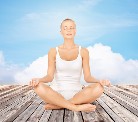chilling: people, relaxation and health concept - woman in underwear meditating in yoga lotus pose Stock Photo