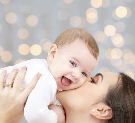 사람, 가족, 어머니와 자녀 개념 - 행복 어머니 휴일을 통해 사랑스러운 아기를 포옹 조명 배경