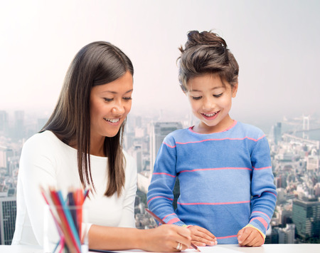 urban parenting: family, children, creativity and happy people concept - happy mother and daughter drawing with pencils over city background