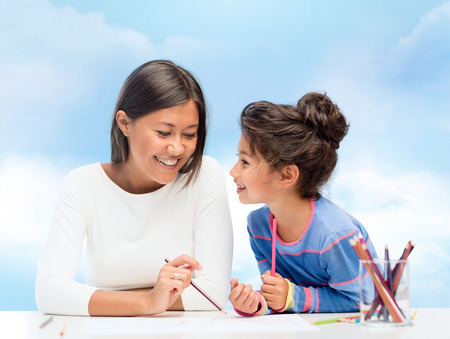 latin mother: family, children and people concept - happy mother and daughter drawing and talking over blue sky background