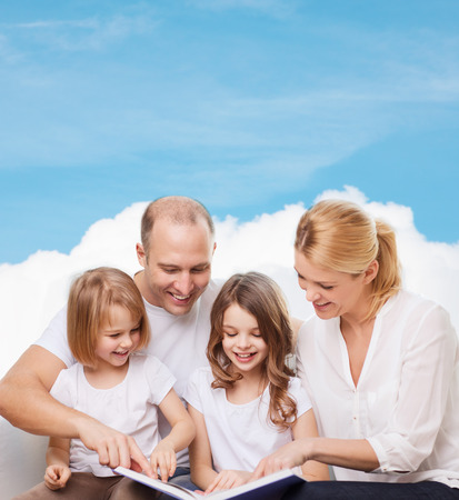 beautiful mom: family, childhood, dream and people - smiling mother, father and little girls reading book over blue sky and cloud background