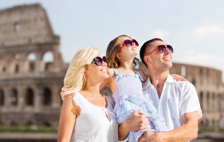 familia abrazo: vacaciones de verano, los viajes, el turismo y la gente concepto - familia feliz en Roma sobre el fondo coliseo
