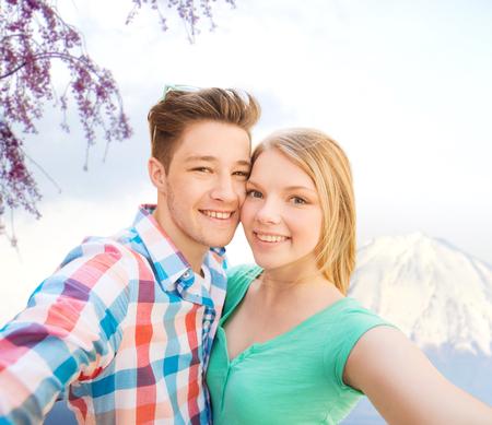 travel, vacation, technology, people and love concept - smiling couple taking selfie with camera or smartphone over japan mountains background photo