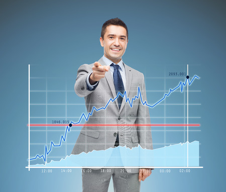 sales executive: business, people and office concept - happy smiling businessman in suit pointing at you over blue background and chart