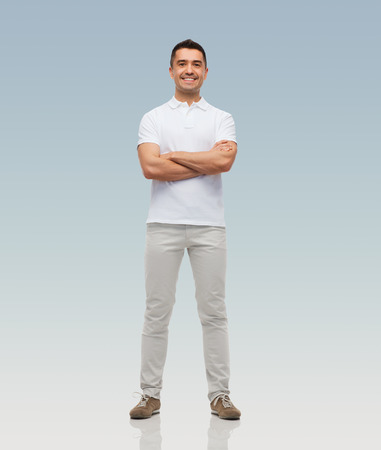 happiness and people concept - smiling man with crossed arms over gray background