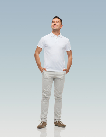 people looking up: happiness and people concept - smiling man with hands in pockets looking up over gray background Stock Photo