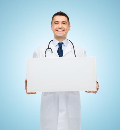 doctoras: cuidado de la salud, la publicidad, la gente y concepto de la medicina - sonriente a m�dico masculino en bata blanca que sostiene la tarjeta en blanco blanco sobre fondo azul