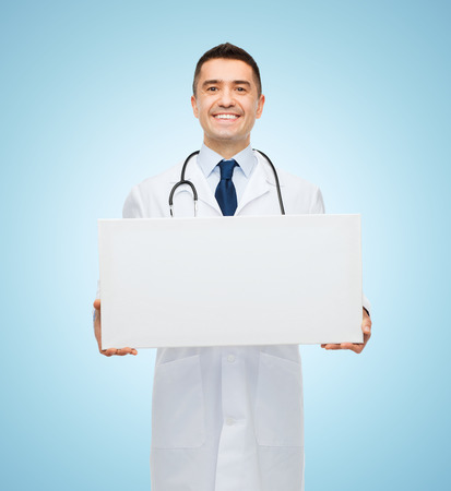 a doctor: healthcare, advertisement, people and medicine concept - smiling male doctor in white coat holding white blank board over blue background