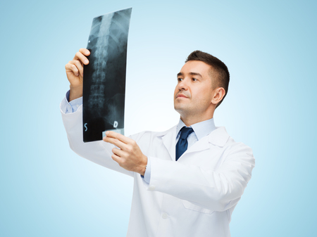 healthcare, roentgen, people and medicine concept - male doctor in white coat looking at x-ray over blue background Stock Photo