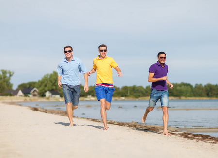 barefoot man: friendship, summer vacation, holidays and people concept - group of smiling male friends in sunglasses running along beach