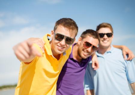 友情、夏休み、休日、人々 コンセプト - ビーチで指差しするサングラスの男性友達に笑顔のグループ